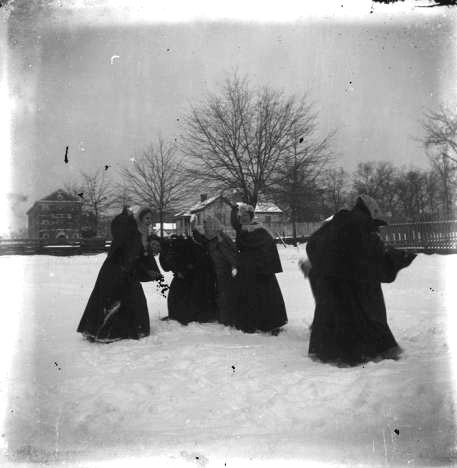Young women playing in the snow on the campus of the Alabama Girls' Industrial School in Montevallo, Alabama ca. 1899