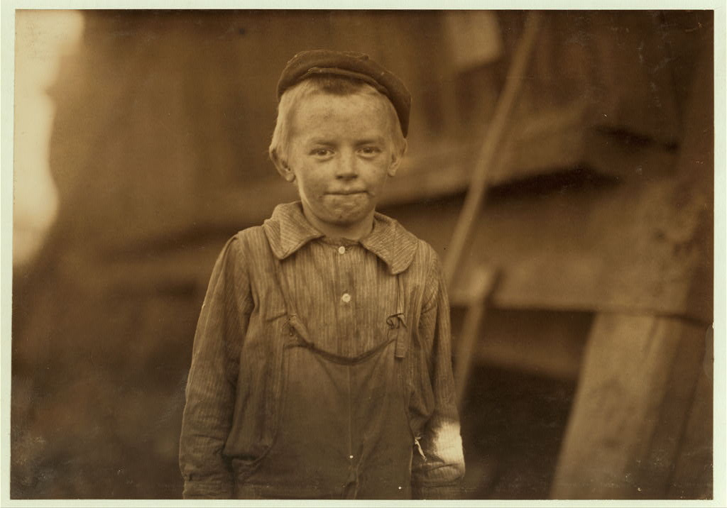 """OUR BABY DOFFER"" they called him. Donnie Cole. Has been doffing for some months. When asked his age, he hesitated, then said, ""I'm Twelve."" Another young boy said ""He can't work unless he's twelve."" Child Labor regulations were conspicuously posted in the mill. Location: Birmingham, Alabama."