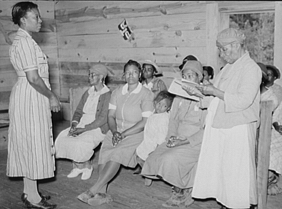 Juanita Coleman (Miss or Mrs.), teacher and NYA (National Youth Administration) leader, listening to one of her pupils in adult class read. She has just learned, is eighty-two years old and best in class. They meet in old church building for reading, writing, arithmetic, and general discussion and educational activities. Gee's Bend, Alabama, photograph by M. P. Walcott