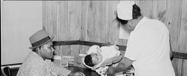 Nurse Shamburg weighing Ira Dencie Pettway's baby in project clinic. Gee's Bend, Alabama