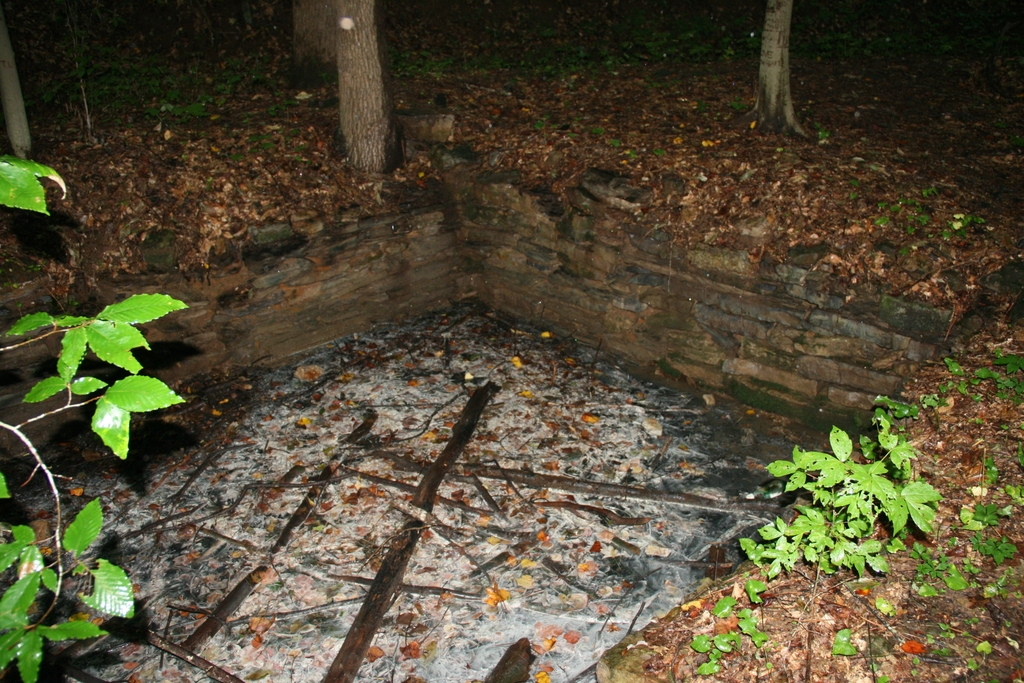 Stone wall surrounding one of the springs that emits white sulfur.