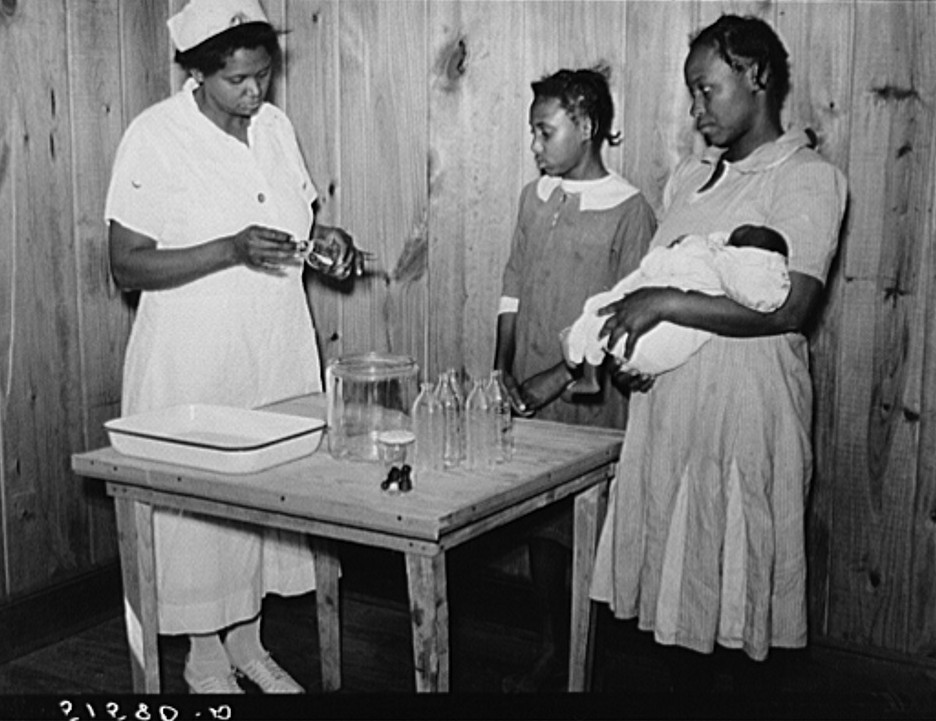 Nurse Shamburg demonstrates care of baby bottles to Mrs. Paralee Coleman and Marie. Mothers have to work in field and children are left at home to care for babies. Health clinic, Gee's Bend, Alabama