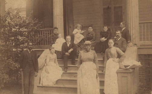 Family_and_servants_on_the_front_porch_of_a_house