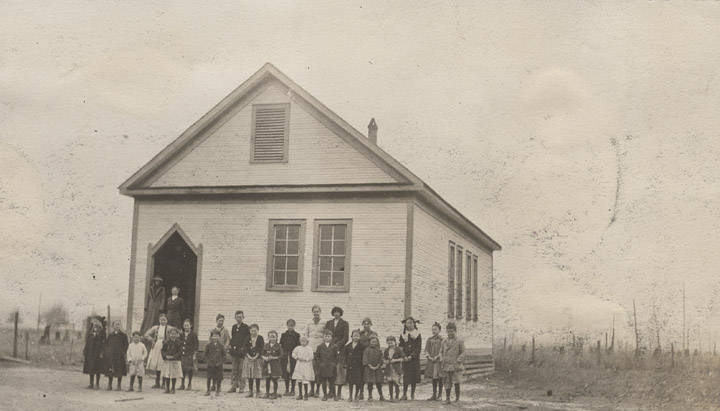 Children_and_adults_in_front_of_a_school_building_in_rural_Baldwin_County_Alabama