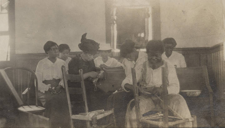 Elderly_African_American_man_showing_teachers_how_to_cane_a_chair_in_a_wooden_church_building_in_Clayton_Alabama
