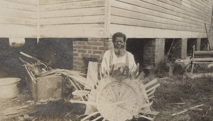 Elderly_African_American_man_weaving_a_basket_outside_a_wooden_church_building_in_Clayton_Alabama