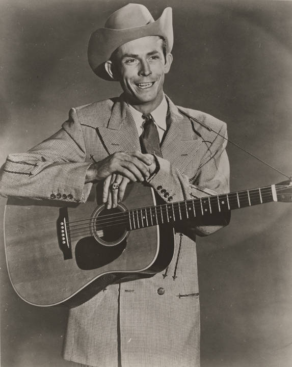 Hank_Williams_wearing_a_houndstooth_jacket_and_holding_a_guitar