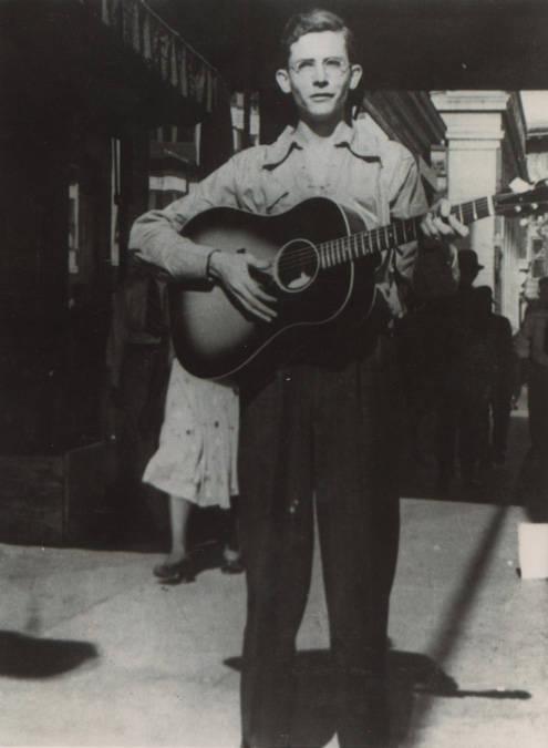 Hank_Williams_with_a_guitar_on_a_sidewalk_in_Montgomery_Alabama