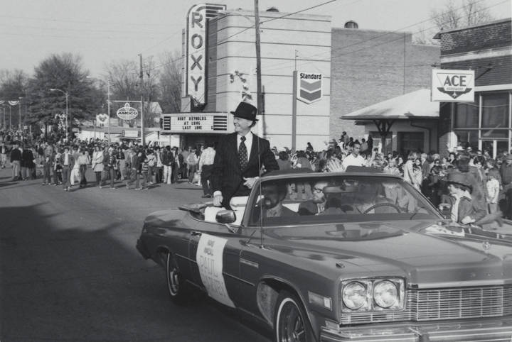 Paul_Harvey_riding_in_a_convertible_as_the_grand_marshal_of_a_Christmas_parade_in_downtown_Russellville_Alabama