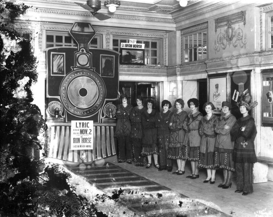 Lyric Theater lobby 1924 with nine women in costume advertising Iron Horse movie (O. V. Hunt - Birmingham Public Library