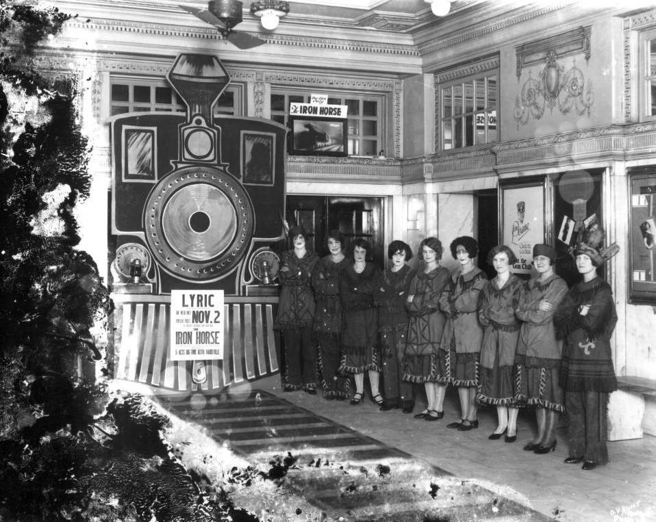 Lyric Theater lobby 1924 with nine women in costume advertising Iron Horse movie (O. V. Hunt - Birmingham Public Library