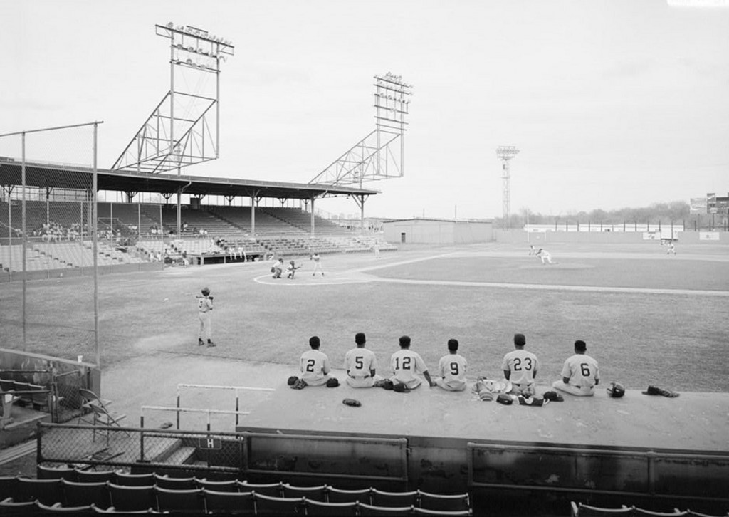VIEW OF PLAYING FIELD WITH HOME PLATE TO CENTER, STANDS IN THE BACKGROUND AND DUGOUT IN THE FOREGROUND, LOOKING WEST