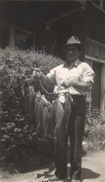 Man holding a line of fish 1939 lollars Q2249
