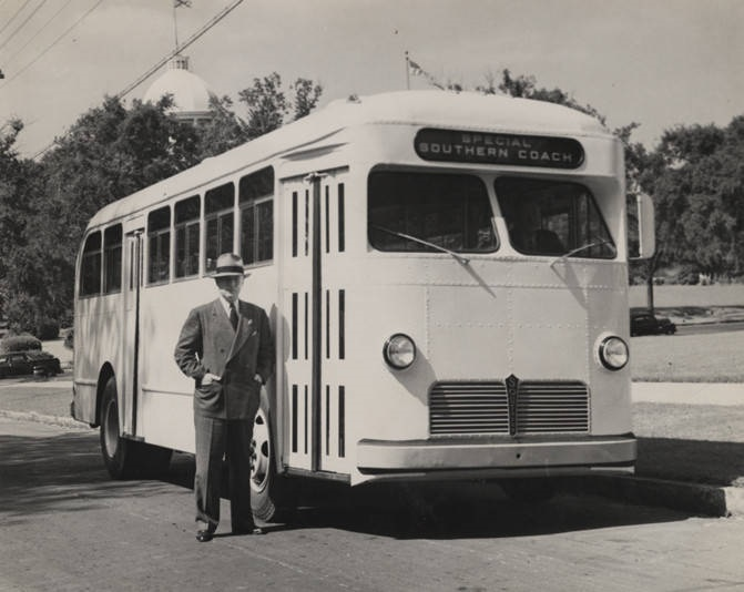 Man_standing_beside_one_of_the_first_buses_built_by_the_Southern_Coach_Manufacturing_Company_in_Evergreen_Alabama Q36706