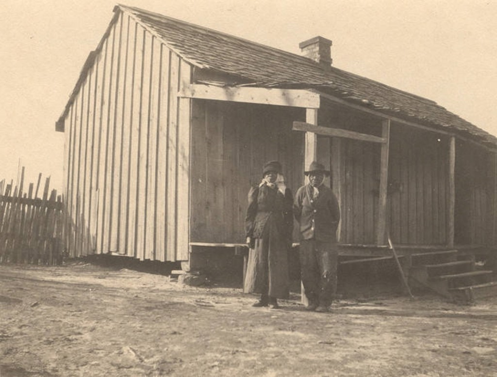 African American man and woman standing in front of a cabin in Crawford, Alabama Q5587