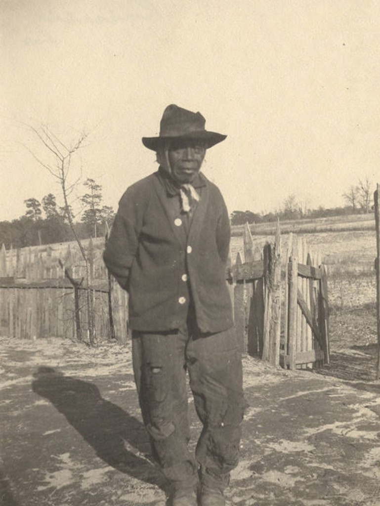 African American man standing in front of a picket fence in Crawford, Alabama Q5577 The same man is in image Q5586.