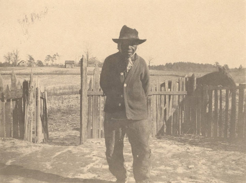 African American man standing in front of a picket fence in Crawford, Alabama.Q5586.
