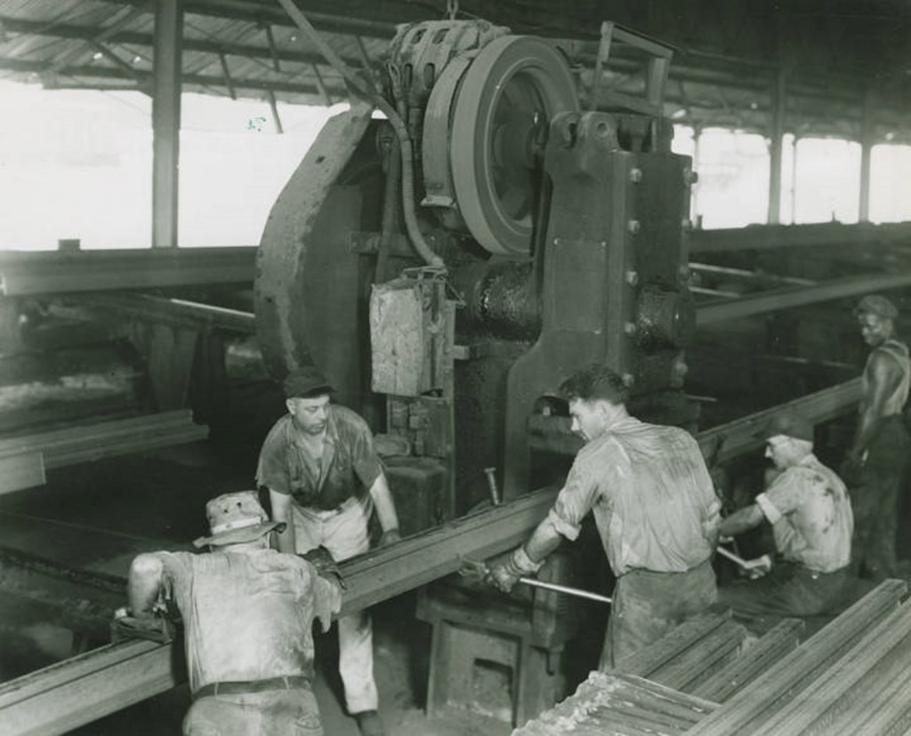 Here workmen at the Ensley Rail Mill straighten a steel rail, which presently will become a portion of track for some southern railroad. ca. 1949 photographer Roy T. Carter, Sr. Birmingham News-Age-Herald Q46227