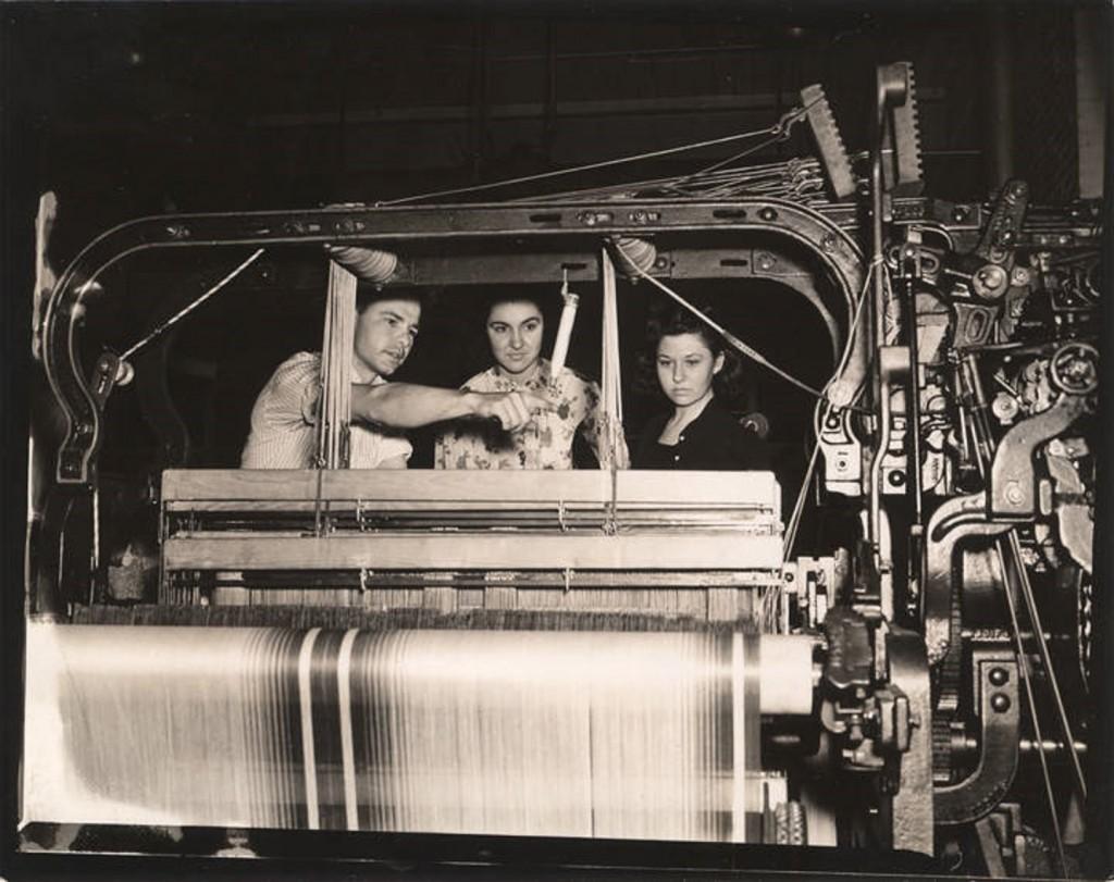 Boy showing girls operation of textile weaving machines ca. 1930s – 1940s – Alabama Polytechnic Institute, Auburn, Alabama Q1985