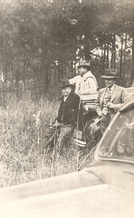 Men sitting or leaning against a vehicle as they watch a fox hunt in Barbour County, Alabama. Mr. Pitts of Pittsview is 86 years old, . ca. 1930s – 1940s Alabama Writers' Project Q2261