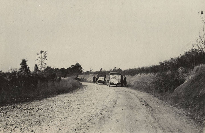 Two cars on the side of a worn macadam road in Mecklenburg County, North Carolina, probably during a cross-country trip to determine the route of the Bankhead Highway. (ADAH) Q10311