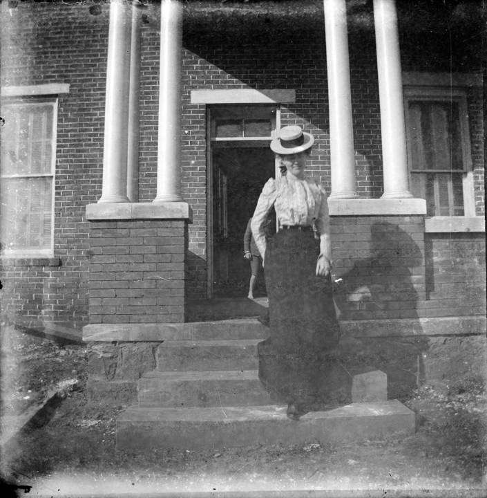 Young woman, probably a student at the Alabama Girls' Industrial School in Montevallo, Alabama, seated on the front porch of the E. S. Lyman home Q40190