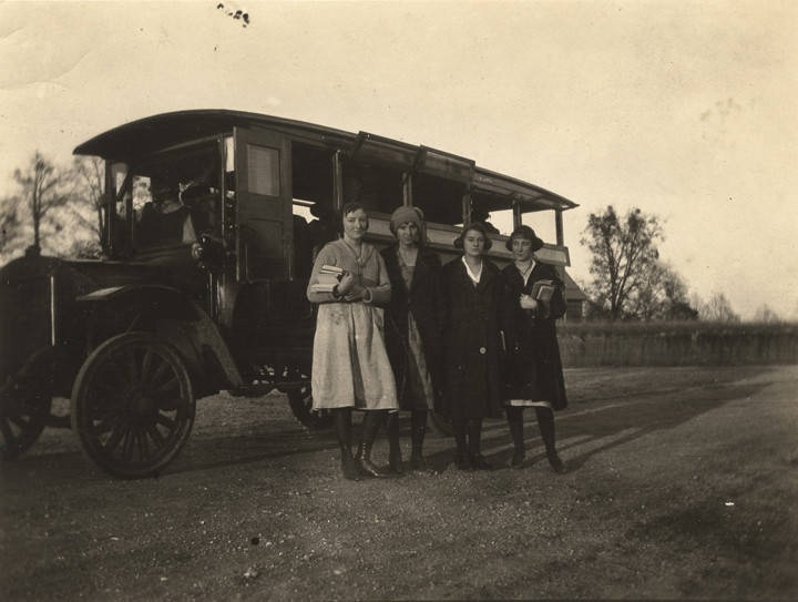 Getting off the bus at their house twelve miles from Ramer High School where they go every day – four female students in Montgomery County, Alabama standing by a school bus ca. 1920 Q3898