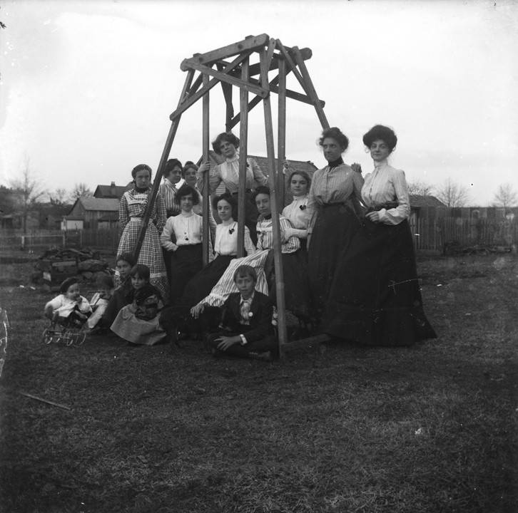Group_of_women_and_children_standing_around_a_wooden_glider_in_a_yard_in_Montevallo_Alabama