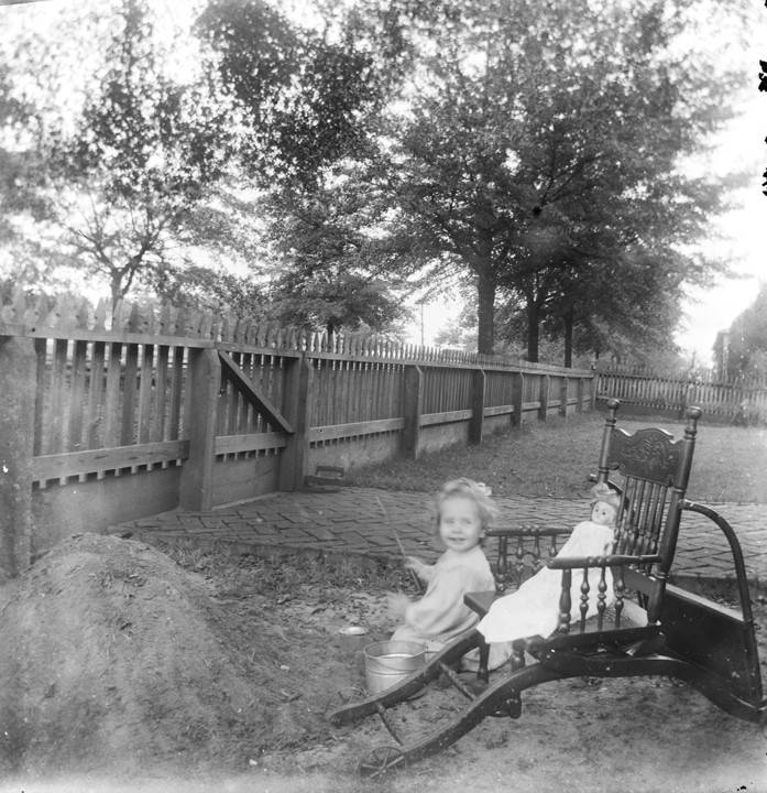 Little_girl_in_a_yard_seated_beside_a_rolling_chair_and_a_pile_of_dirt