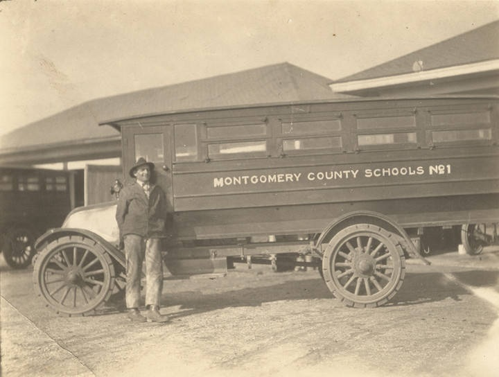 Man standing in front of a Montgomery County school bus in Montgomery, Alabama. Bus #1 was completing seven years of hard running and is still working a fine record ca. 1920 Q3875
