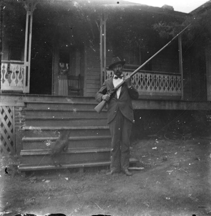 Man_holding_a_rifle_while_standing_in_the_yard_in_front_of_a_house_in_Montevallo_Alabama