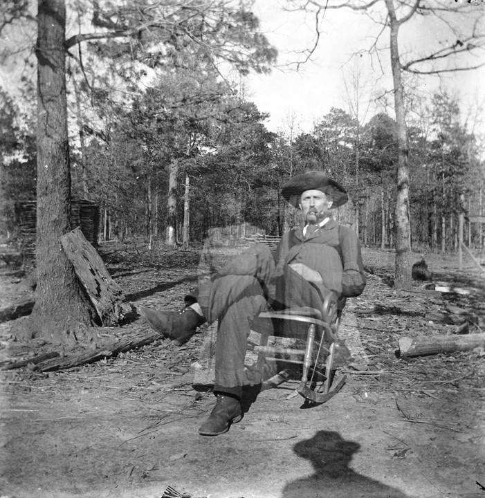 Man_seated_in_a_rocking_chair_in_a_dirt_yard_in_Montevallo_Alabama