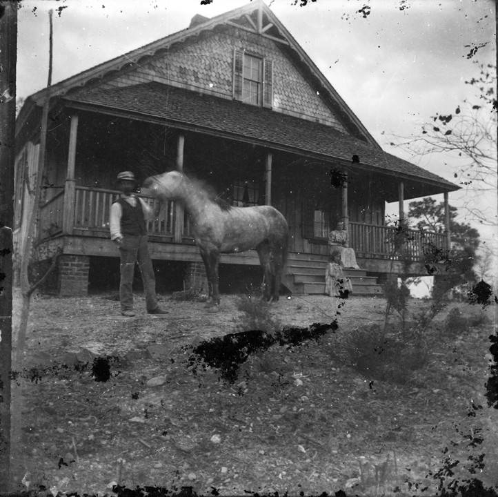 Man_standing_with_a_horse_in_the_front_yard_of_a_house_in_Montevallo_Alabama