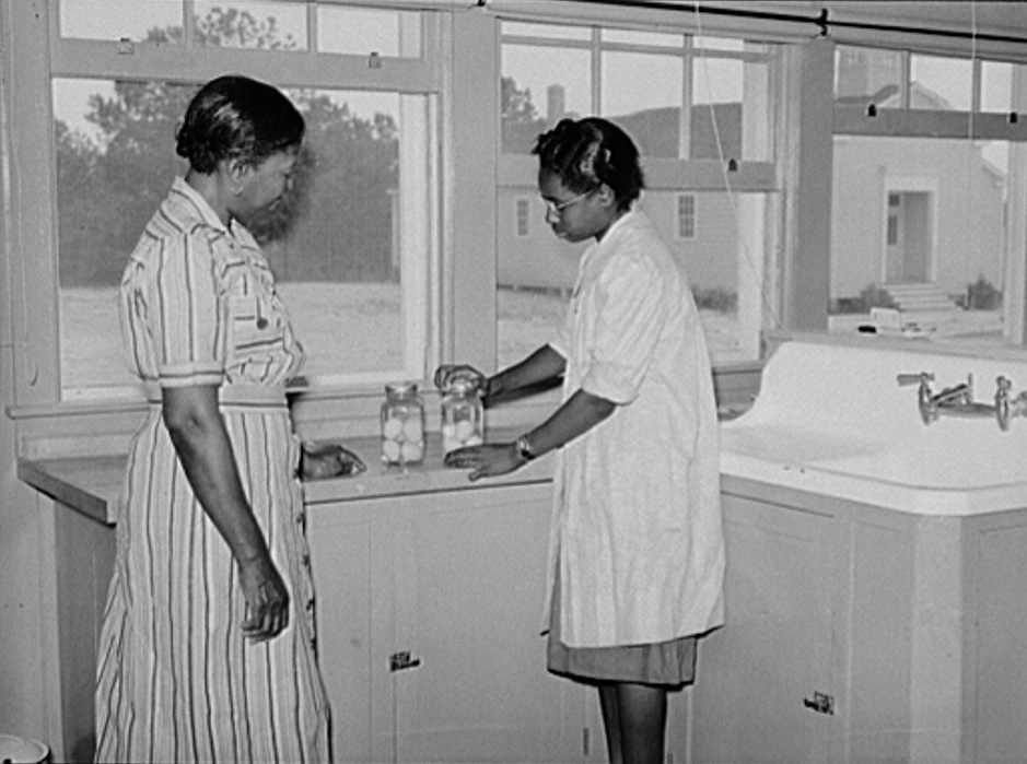 Juanita Coleman, NYA (National Youth Administration) leader and teacher, helps Sally Titus preserve some eggs.