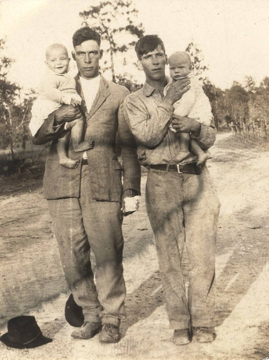 Two Cajun men holding babies in Mobile County, Alabama Q5418