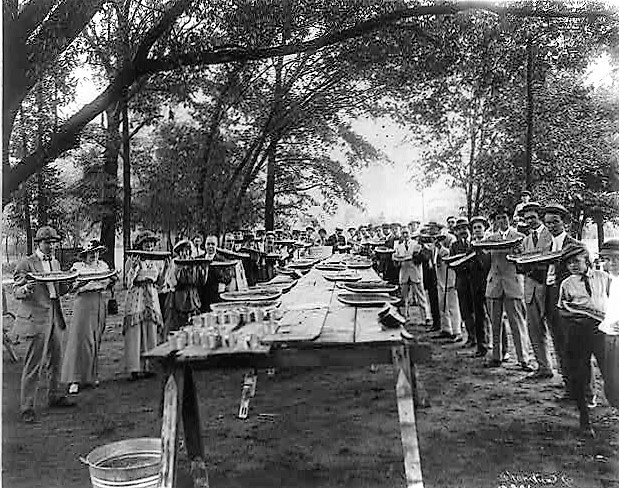 Commercial Club 1917 holding large pieces of watermelons posed, standing around tables, Fairfield, Alabama.(Library of Congress)
