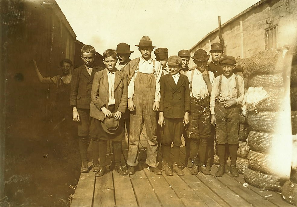 Group of boys working in Woodstock Cotton Mills. Smallest boy is Will Earwood, said he had been working there six years.g1910 by Lewis Wickes Hine (Library of Congress)