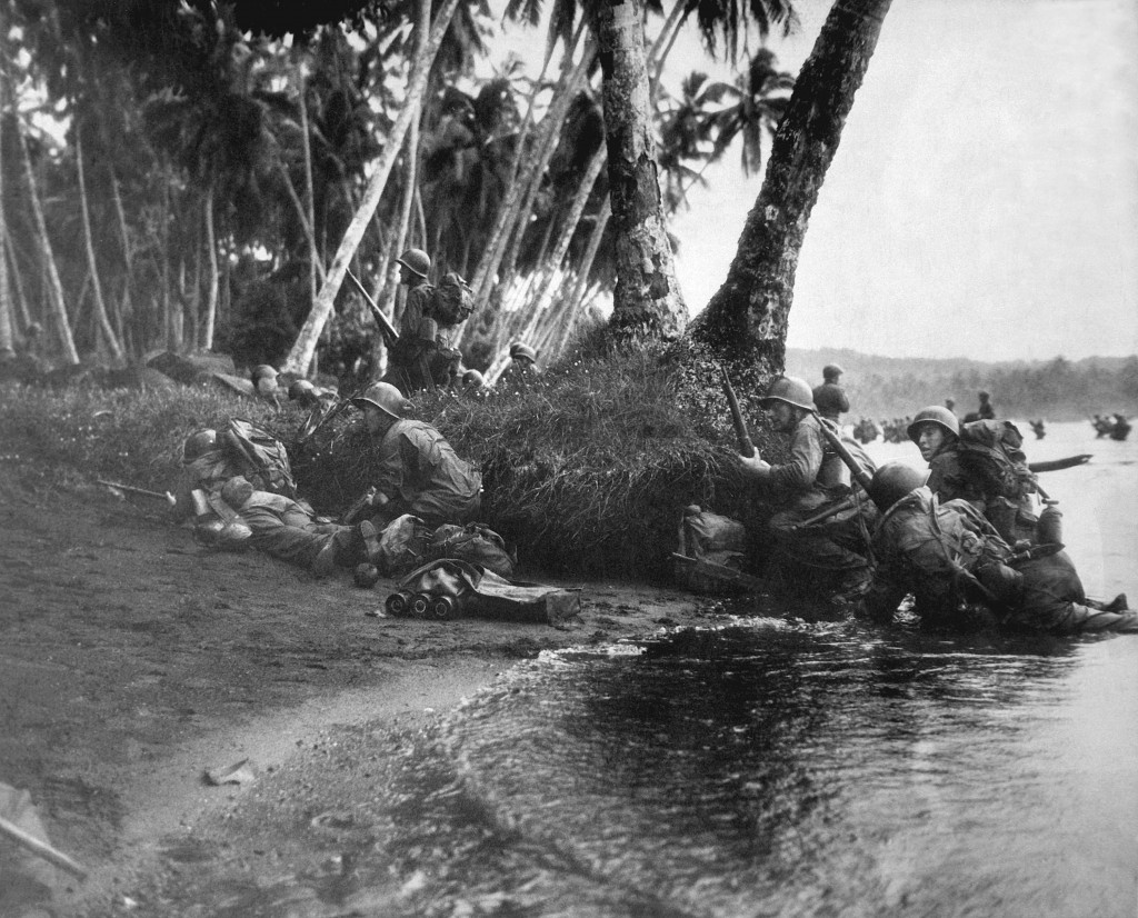 Landing operations on Redova Island, Solomon Islands, 30 June 1943. Attacking at the break of day in a heavy rainstorm, the first Americans ashore huddle behind tree trunks and any other cover they can find. (Navy) NARA FILE #: 080-G-52573 WAR & CONFLICT BOOK #: 1176