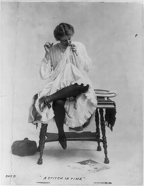 A Stich in Time -Woman seated on small table with legs crossed, mending dress, which she is wearing ca. 1890 (Library of Congress)