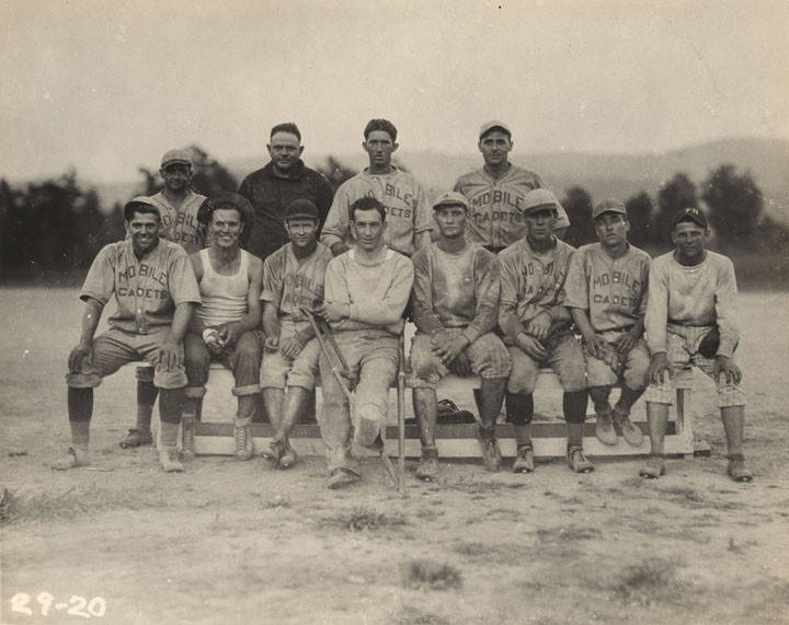 Men on a baseball team at the Air Corps base at Roberts Field in Birmingham, Alabama. ca. 1920s – Most of the men in the group are wearing shirts that say, Mobile Cadets.