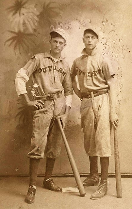 Two young men in baseball uniforms. Their shirts say Outlaw ca. 1900 – Duke and Weeks family collection Q9479 ,