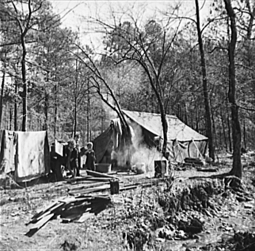 Tent occupied by sharecropper family now living in a migrant camp near Birmingham, Alabama. Note water supply at right (Library of Congress)