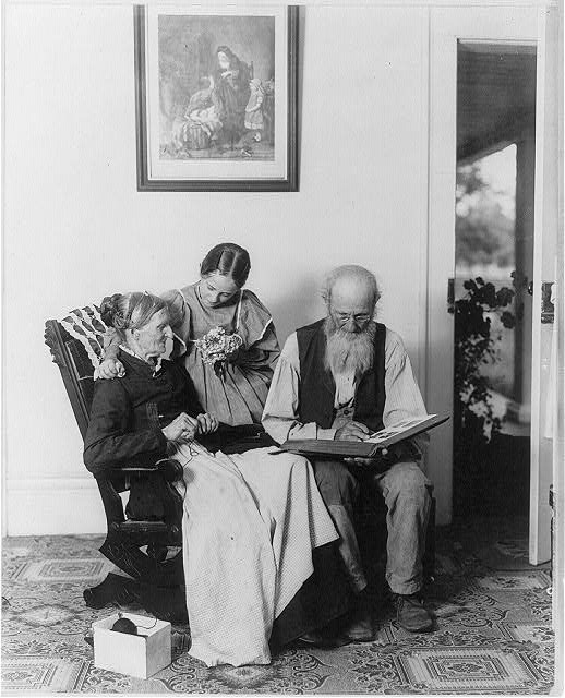 Grandma's birthday -Elderly woman knitting and elderly man looking at photo album. 1899 (Library of Congress