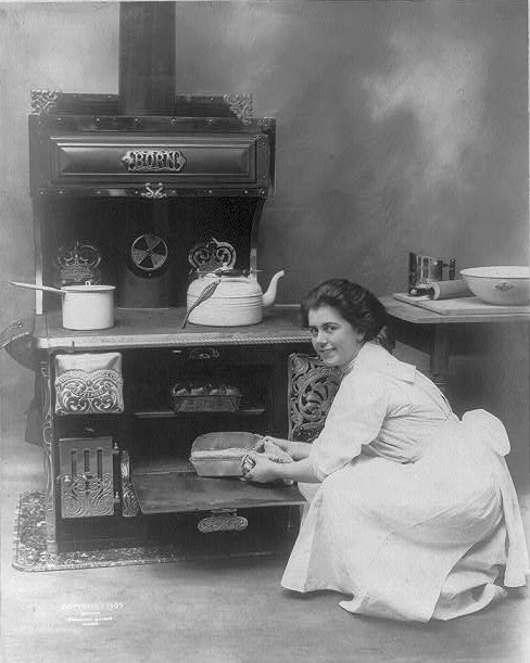 young-woman-removing-a-loaf-of-bread-from-an-oven-made-by-the-born-range-co-1909-library-of-congress