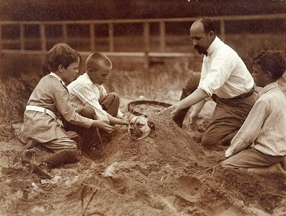 Photograph showing Quentin, Archie, and Nicholas Roosevelt, with Walter Russell, burying a dog in the sand at Sagamore Hill (2)